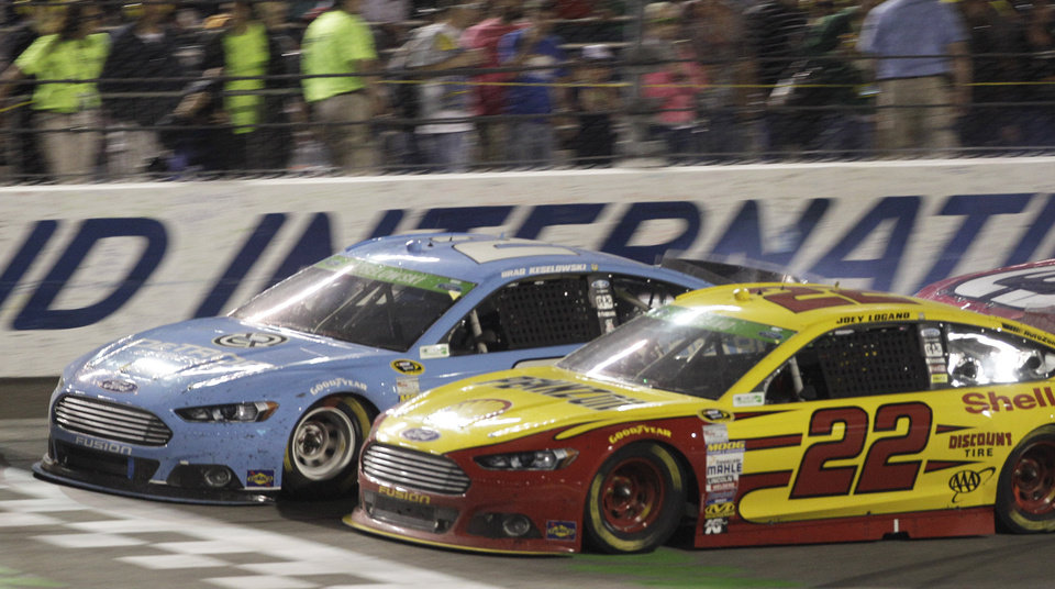 Photo - Joey Logano (22) and Brad Keselowski (2) approach the start-finish line in the closing laps of the NASCAR Sprint Cup Auto race at Richmond International Raceway in Richmond, VA., Saturday, April 26, 2014. Logano won the race. (AP Photo/Steve Helber)