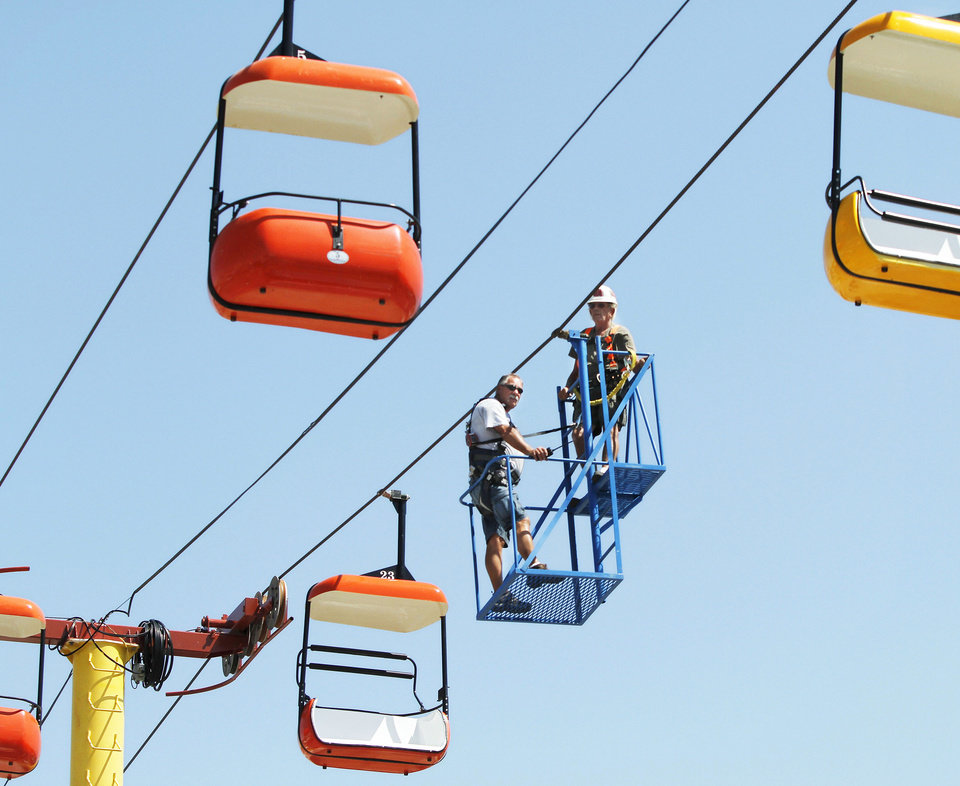 Photo - Above left: A carnival ride operator and an inspector from the Oklahoma Labor Department check the sky tram towers and cables Wednesday while setting up for Oklahoma State Fair. The 11-day event begins Thursday and ends Sept. 23.