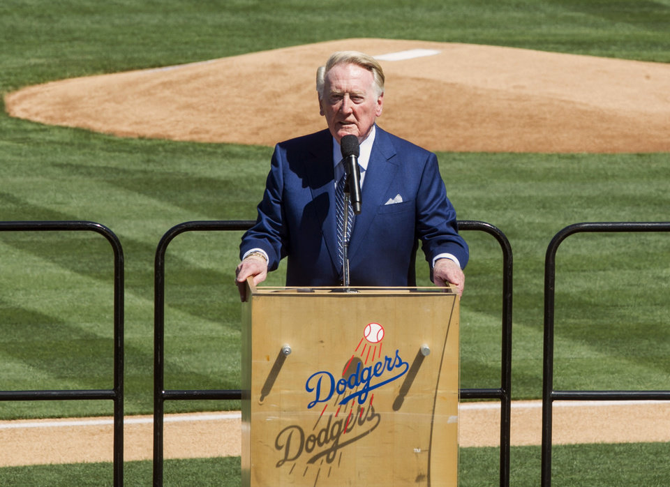 Photo - Los Angeles Dodgers announcer Vin Scully leads an eulogy for late Dr. Frank Jobe during a memorial service at Dodger Stadium in Los Angeles Monday, Apr. 7, 2014. Dr. Frank Jobe, was the surgeon who pioneered the elbow procedure that became known as Tommy John surgery and saved the careers of countless pitchers. Jobe died last month at 88. (AP Photo/Damian Dovarganes)
