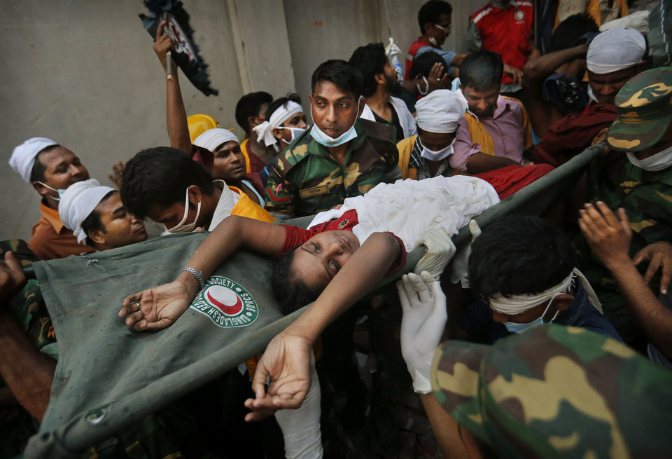 Photo - A Bangladeshi woman survivor is carried from the rubble by rescuers at the site of a building that collapsed Wednesday in Savar, near Dhaka, Bangladesh, Thursday, April 25, 2013. By Thursday, the death toll reached at least 194 people as rescuers continued to search for injured and missing, after a huge section of an eight-story building that housed several garment factories splintered into a pile of concrete.(AP Photo/Kevin Frayer)