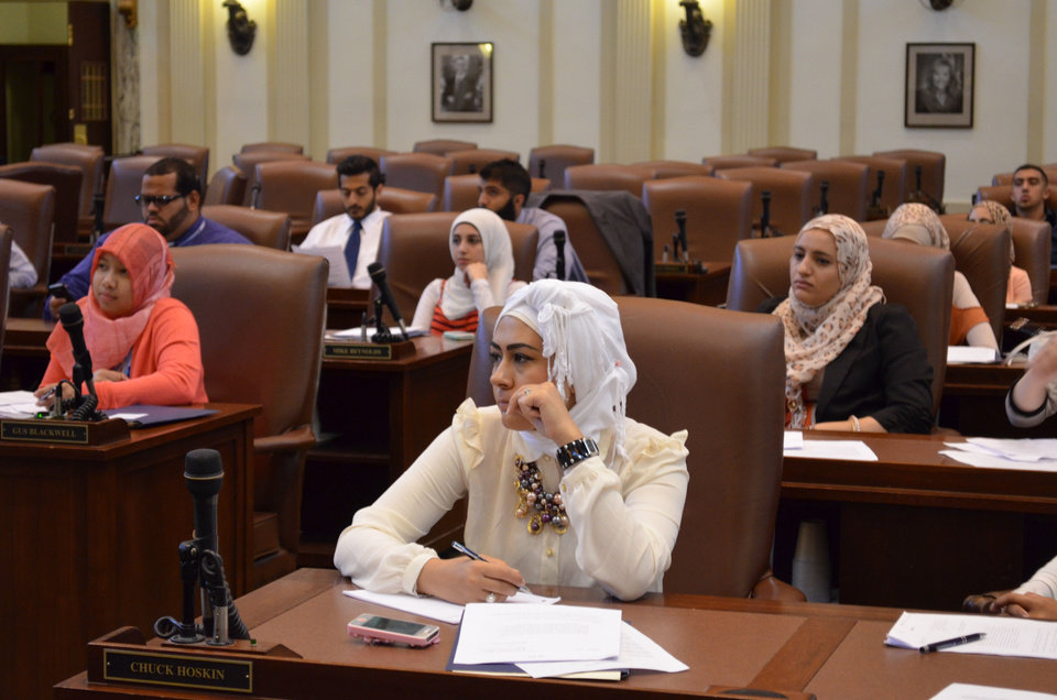 Photo - Nour Agha of Tulsa, center, listens during a mock legislative debate at the state Capitol, held as part of a recent Muslim Youth Leadership Symposium hosted by the Council on American-Islamic Relations-Oklahoma City.