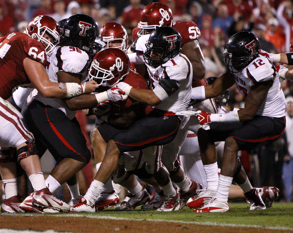 Oklahoma's Roy Finch (22) is stopped short of the end zone by Texas Tech's Dennell Wesley (96) and Texas Tech's Terrance Bullitt (1) during the college football game between the University of Oklahoma Sooners (OU) and the Texas Tech University Red Raiders (TTU) at Gaylord Family-Oklahoma Memorial Stadium in Norman, Okla., Saturday, Oct. 22, 2011. Photo by Bryan Terry, The Oklahoman
