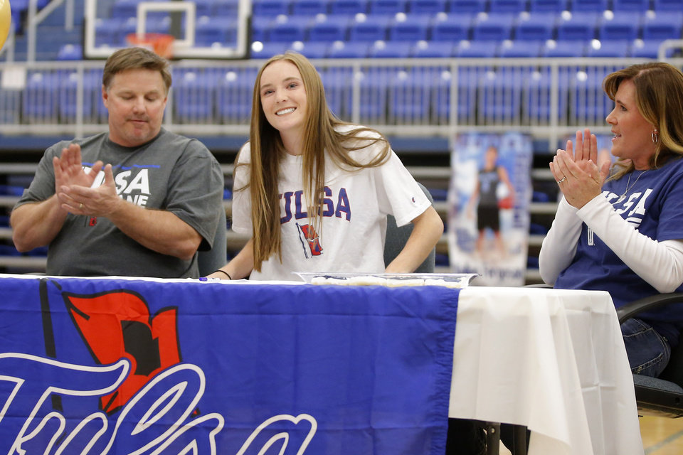 Photo - Deer Creek soccer player Grayson Schimmels smiles after signing a letter of intent to play soccer at University of Tulsa as her parents Donnie and Carrie Schimmels watch during a signing day ceremony at Deer Creek High School, Wednesday, Feb. 7, 2018. Photo by Bryan Terry, The Oklahoman