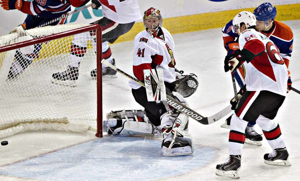Photo - Ottawa Senators goalie Craig Anderson (41) watches the puck go in the net as Erik Karlsson (65) and Edmonton Oilers' Taylor Hall (4) battle in front during the second period of an NHL hockey game, Tuesday, March 4, 2014 in Edmonton, Alberta. (AP Photo/The Canadian Press, Jason Franson)