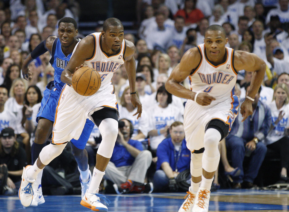 Photo -   Oklahoma City Thunder forward Kevin Durant, center, heads upcourt with teammate Russell Westbrook, right, and Dallas Mavericks center Ian Mahinmi, left, in the second quarter of Game 2 in the first round of the NBA basketball playoffs, in Oklahoma City, Monday, April 30, 2012. (AP Photo/Sue Ogrocki)