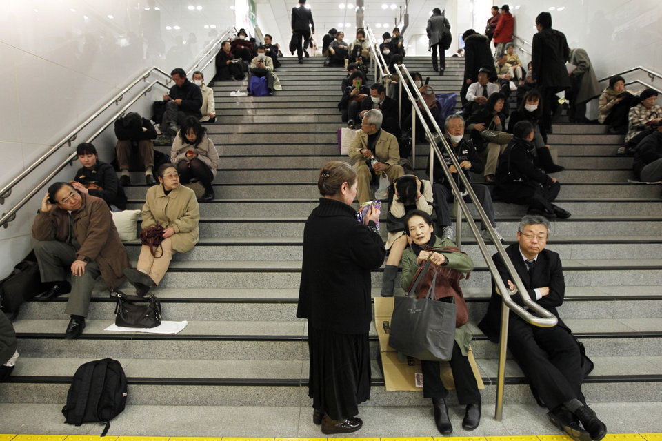 Photo - Commuters sit stranded at Tokyo railway station as train services are suspended due to a powerful earthquake Friday, March 11, 2011. The largest earthquake in Japan's recorded history slammed the eastern coasts Friday. (AP Photo/Hiro Komae) ORG XMIT: TTX105