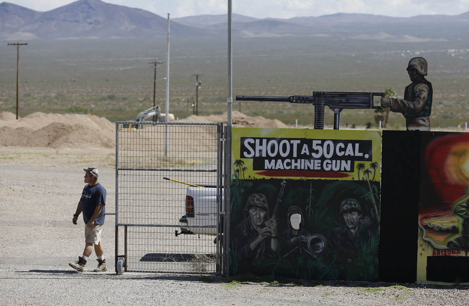 Photo - A man closes off an entrance to the Last Stop outdoor shooting range Wednesday, Aug. 27, 2014, in White Hills, Ariz. Gun range instructor Charles Vacca was accidentally killed Monday, Aug. 25, 2014 at the range by a 9-year-old with an Uzi submachine gun. (AP Photo/John Locher)