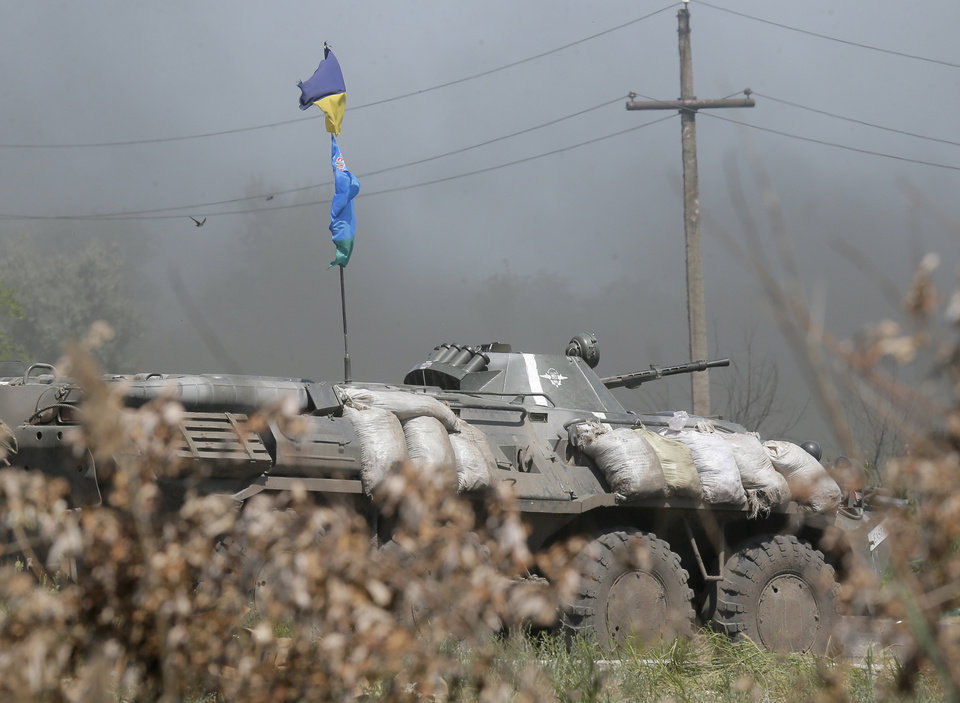 Photo - A Ukrainian APC move to position during a battle with pro-Russian separatist fighters at Slovyansk, Ukraine, Friday, June 6, 2014. At least five Ukrainian soldiers were wounded, two of them heavily in this short clash with the pro-Russian separatist fighters. (AP Photo/Efrem Lukatsky)