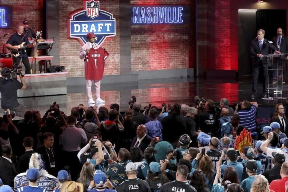Photo -  Oklahoma quarterback Kyler Murray shows off his new jersey after the Arizona Cardinals selected Murray in the first round at the NFL football draft, Thursday, April 25, 2019, in Nashville, Tenn. (AP Photo/Gregory Payan)