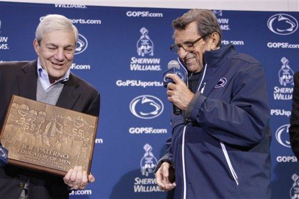 Penn State President Graham Spanier, left, presents head football coach Joe Paterno with a plague commemorating his 409th collegiate win after an NCAA college football game against Illinois in State College, Pa., Saturday, Oct. 29, 2011. Penn State won 10-7. (AP Photo/Gene J. Puskar)