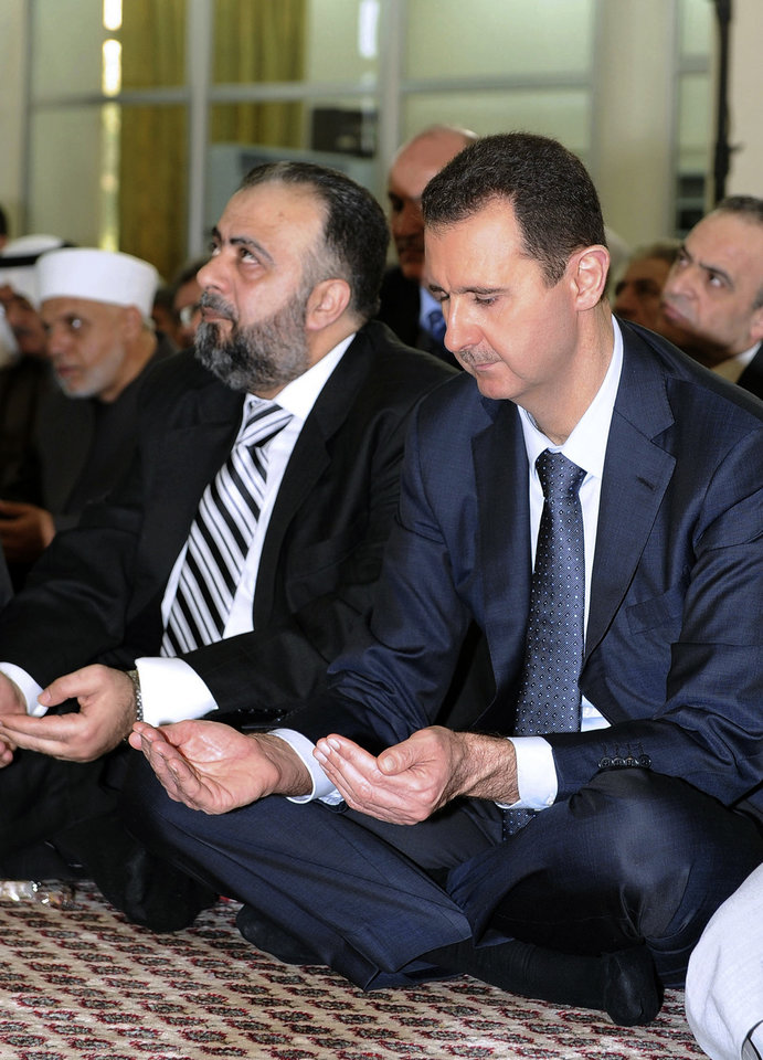 Photo -   In this photo released by the Syrian official news agency SANA, Syrian president, Bashar Assad, performs Eid prayers in the Hamad Mosque in Damascus, Syria, Sunday, Aug. 19, 2012. Assad prayed early on Sunday at the start of Eid al-Fitr, a three-day holiday marking the end of the holy month of Ramadan. The last time he appeared in public was on Wednesday, July 4, 2012 when he gave a speech in parliament. (AP Photo/SANA)