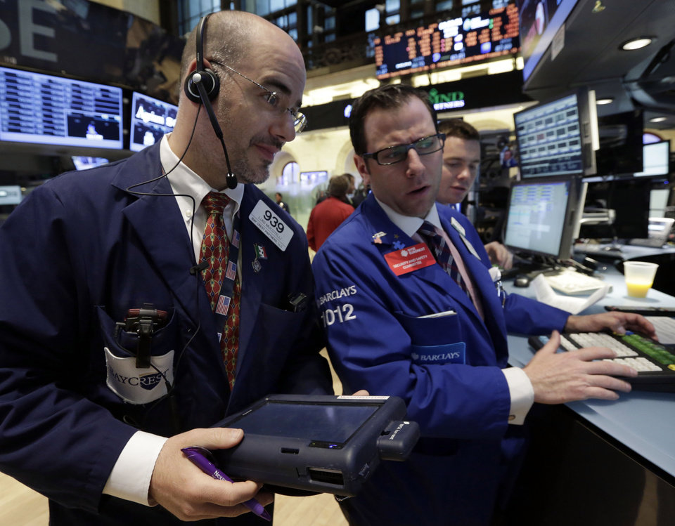 Photo - Trader Luigi Muccitelli, left, and specialist Michael Pistillo, center, work on the floor of the New York Stock Exchange Monday, April 29, 2013.  A pair of encouraging economic reports helped propel the stock market up in early trading on Monday. (AP Photo/Richard Drew)