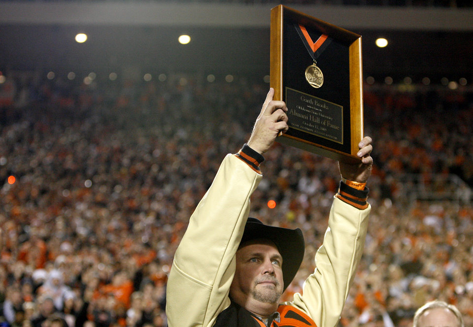 Photo - Garth Brooks hoists the Alumni Hall of Fame Plaque during the college football game between Oklahoma State University (OSU) and the University of Missouri (MU) at Boone Pickens Stadium in Stillwater, Okla. Saturday, Oct. 17, 2009.  Photo by Sarah Phipps, The Oklahoman