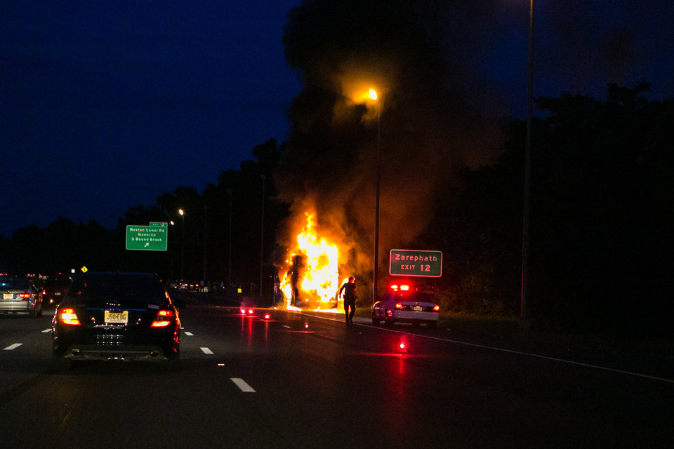 Photo - In this photo provided by James Kastner, a tour bus caught fire on a busy stretch of New Jersey highway, but no passengers were injured in Bridgewater, N.J., Saturday, July 19, 2014. State Police Sgt. Brian Polite says the fire was reported at about 8:40 p.m. Initial reports say passengers were seen running along the southbound lanes of Interstate 287, away from the blaze. There's no word yet on what caused the fire. (AP Photo/Jimmy Kastner) MANDATORY CREDIT