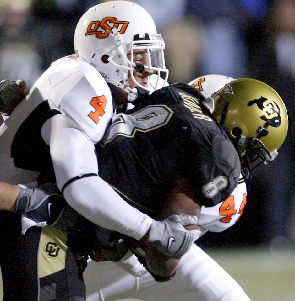 Photo - OSU's Patrick Lavine brings down Colorado's Demetrius Sumler during the college football game between Oklahoma State University and the University of Colorado at Folsom Field in Boulder, Colo., Saturday, Nov. 15, 2008. BY BRYAN TERRY, THE OKLAHOMAN