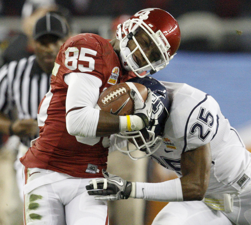 Photo - Oklahoma's Ryan Broyles (85) is hit by Connecticut's Harris Agbor (25) during the Fiesta Bowl college football game between the University of Oklahoma Sooners and the University of Connecticut Huskies in Glendale, Ariz., at the University of Phoenix Stadium on Saturday, Jan. 1, 2011.  Photo by Bryan Terry, The Oklahoman