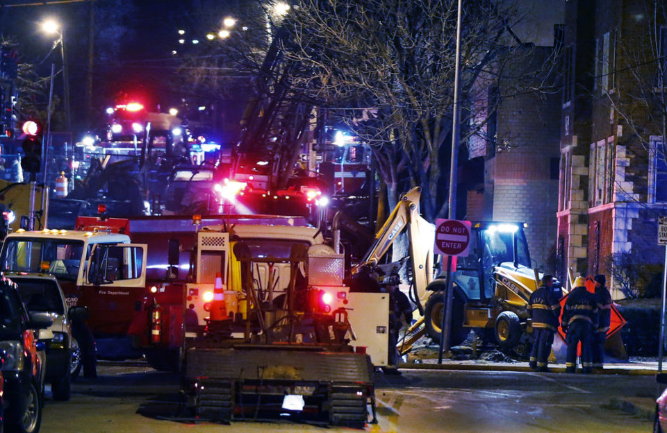 Firemen and utility workers respond to a gas explosion and massive fire Tuesday night, Feb. 19, 2013 in the Plaza shopping district in Kansas City, Mo. A car crashed into a gas main in the upscale Kansas City shopping district, sparking a massive blaze that engulfed an entire block and caused multiple injuries, police said (AP Photo/Orlin Wagner)