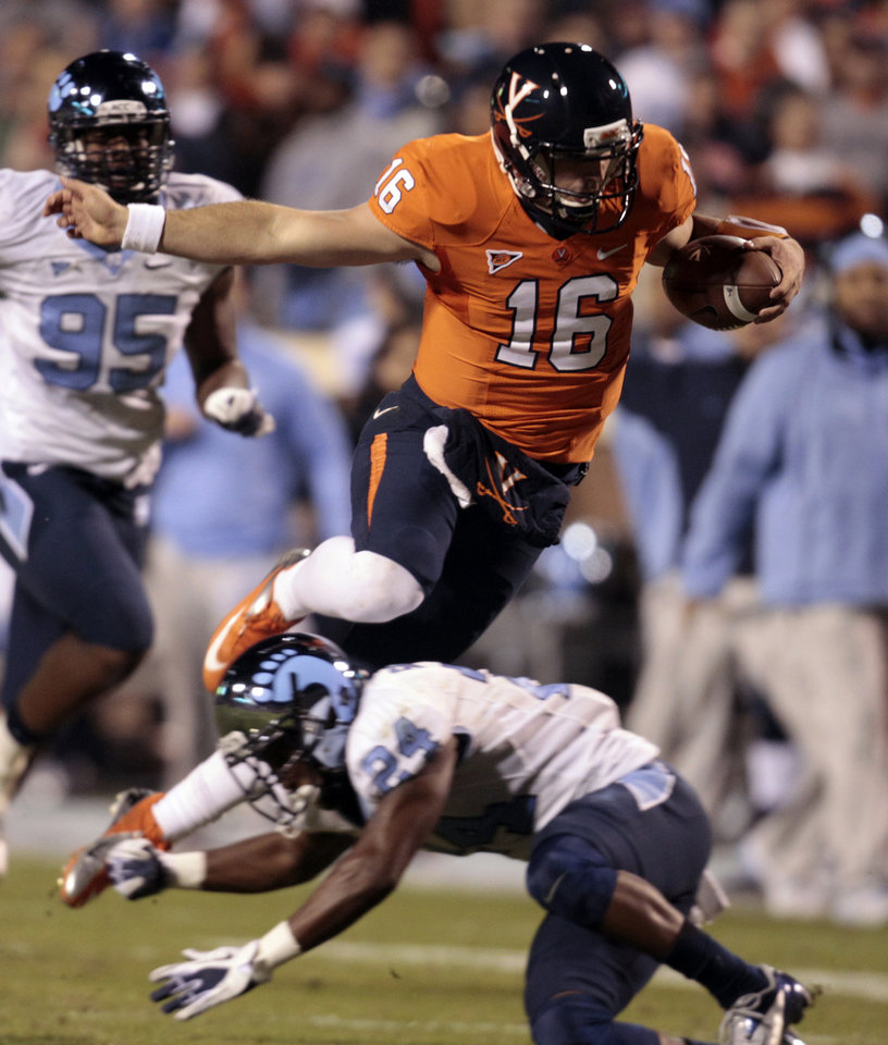Photo -   Virginia quarterback Michael Rocco (16) hurdles North Carolina cornerback Terry Shankle (24) during the first half of an NCAA college football game at Scott stadium Thursday, Nov. 15, 2012 in Charlottesville, VA (AP Photo/Steve Helber)