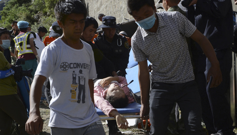 Photo - In this photo released by China's Xinhua News Agency, an injured passenger rescued from an overturned tour bus after it fell off a 10-meter (30-foot) cliff is carried on a stretcher in Nyemo County, southwest China's mountainous region of Tibet Saturday, Aug. 9, 2014. Xinhua reported the bus carrying about 40 people careened after it crashed in a pileup involving a sports utility vehicle and a pickup truck on a state road. Casualty details were not immediately known. (AP Photo/Xinhua, Chogo) NO SALES