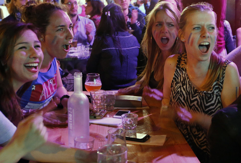 Photo - French soccer supporters react as they watch a live broadcast of the group E World Cup soccer match between Switzerland and France, at the Metro 14th District bar in Paris, France, Friday, June 20, 2014. The match ended in a 5-2 win for France. (AP Photo/Francois Mori)
