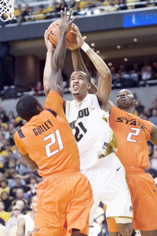 Photo - Missouri's Laurence Bowers, center, shoots the ball between OSU's Fred Gulley, left, and Obi Muonelo during the Cowboys' loss to the Tigers on Saturday. AP photo
