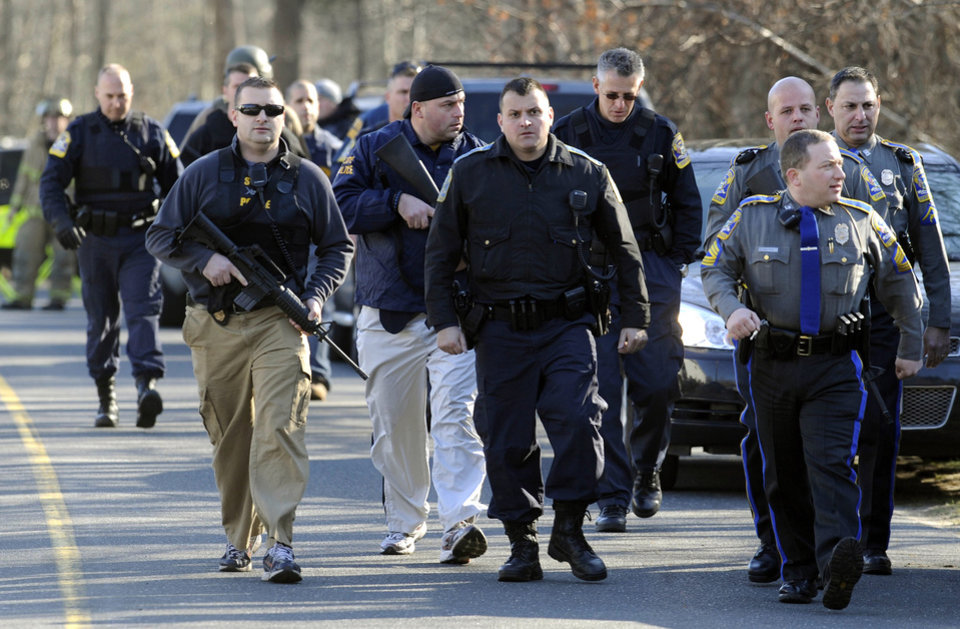 Photo - Law enforcement canvass the area following a shooting at the Sandy Hook Elementary School in Newtown, Conn., about 60 miles (96 kilometers) northeast of New York City, Friday, Dec. 14, 2012. An official with knowledge of Friday's shooting said 27 people were dead, including 18 children.  (AP Photo/Jessica Hill)