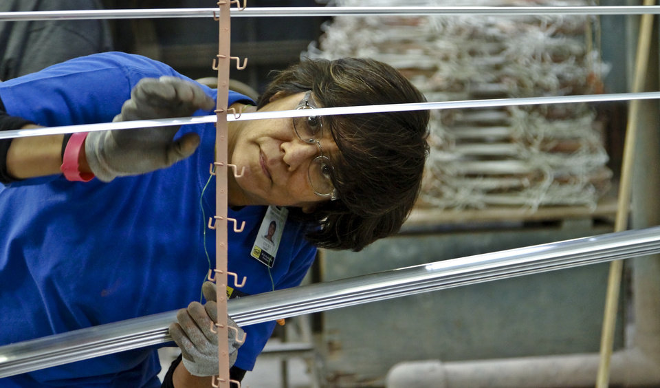 Magdalena Lucio prepares aluminum strips to be powder coated at the MD Building Products plant on Wednesday, Jan. 2, 2013, in Oklahoma City, Okla. Photo by Chris Landsberger, The Oklahoman