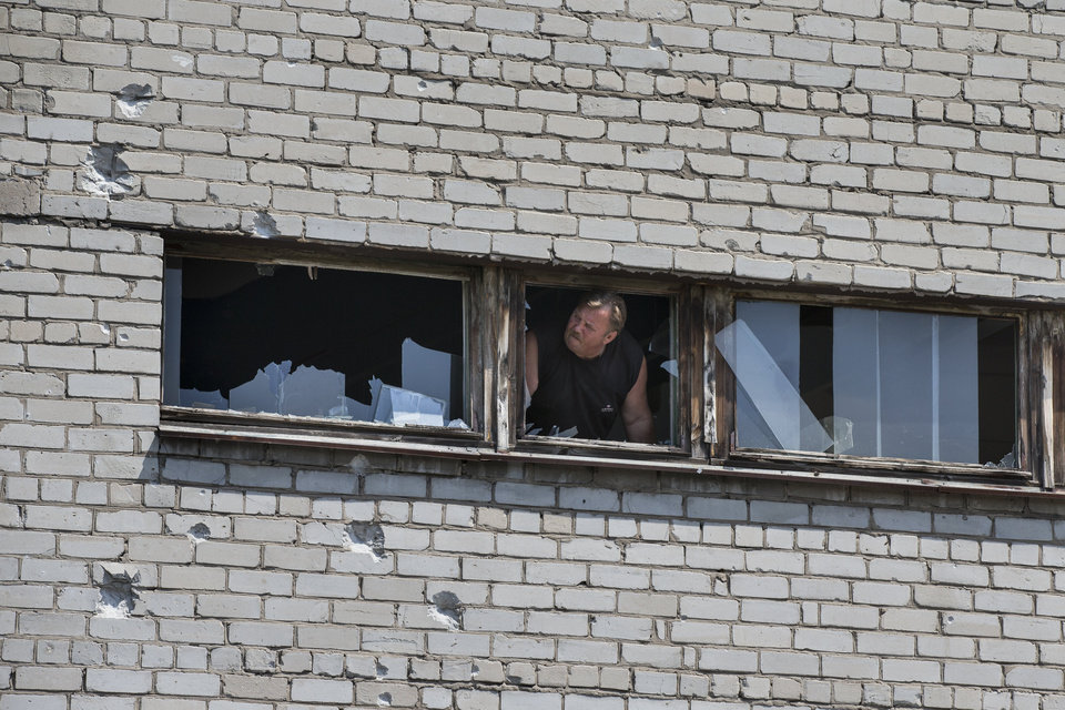 Photo - A man looks at school buildings damaged by shrapnel following a shelling from Ukrainian government forces, in Slovyansk, Ukraine, Wednesday, May 28, 2014.   In Slovyansk, a city about 90 kilometers (55 miles) north of Donetsk which has been the scene of consistent clashes over the past few weeks, after residential areas on Wednesday came under mortar shelling from the government forces, with several people wounded and some buildings damaged in the attack. (AP Photo/Alexander Zemlianichenko)