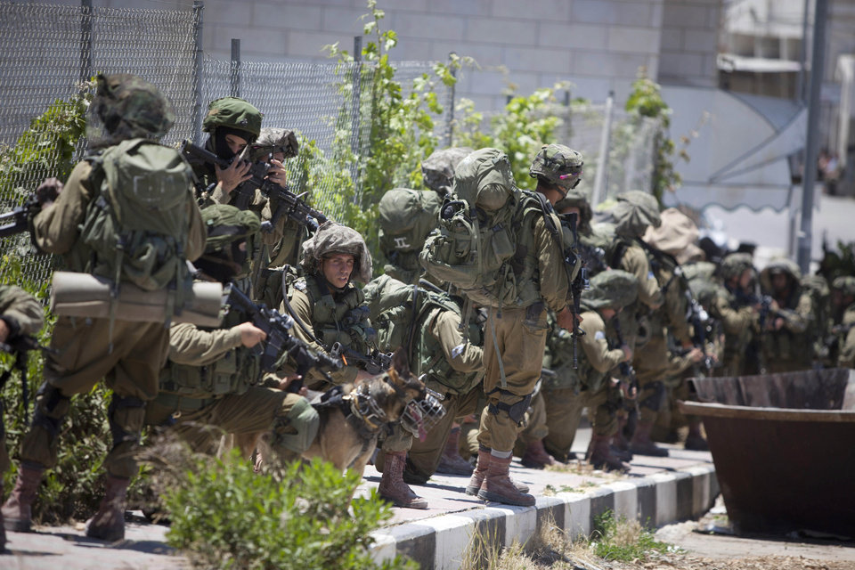 Photo - Israeli soldiers patrol during a military operation to search for three missing teenagers outside the West Bank city of Hebron, Sunday, June 15, 2014. Israeli troops on Sunday arrested some 80 Palestinians, including dozens of members of Hamas, in an overnight raid in the West Bank as Prime Minister Benjamin Netanyahu accused the Islamic militant group of kidnapping three teenagers who went missing nearly three days ago. (AP Photo/Majdi Mohammed)