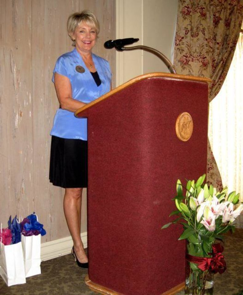 GATHERING OF ANGELS... Pi Beta Phi Alumnae President Mary Reneau welcomes guests. (Photo by Helen Ford Wallace).