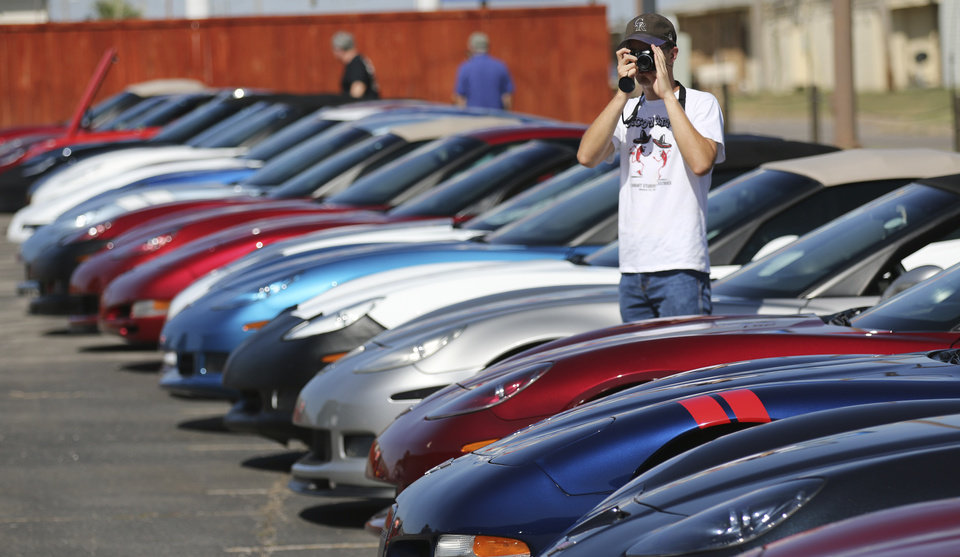 Photo - Nathaniel Kliewer takes photos of Chevrolet Corvettes on display at Frontier Chevrolet in El Reno, Monday August  25, 2014. Corvette enthusiast made a stop in El Reno on their cross country trip in National Corvette Caravan.  Photo By Steve Gooch, The Oklahoman