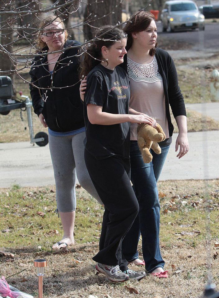 Photo - Stacey Barfield, mother of Hailey Owens, center, takes a teddy bear from the makeshift memorial  Thursday, Feb. 20, 2014 near the site where the 10-year-old girl was abducted just blocks from her Springfield, Mo., home. Prosecutors have charged Craig Michael Wood with first-degree murder, kidnapping and armed criminal action in their girls death. Prosecutors says the fourth-grader's body was found stuffed in two trash bags inside plastic storage containers in the basement of Wood's Springfield home. She had been shot in the head.. (AP Photo/The Springfield News-Leader, Dean Curtis) NO SALES