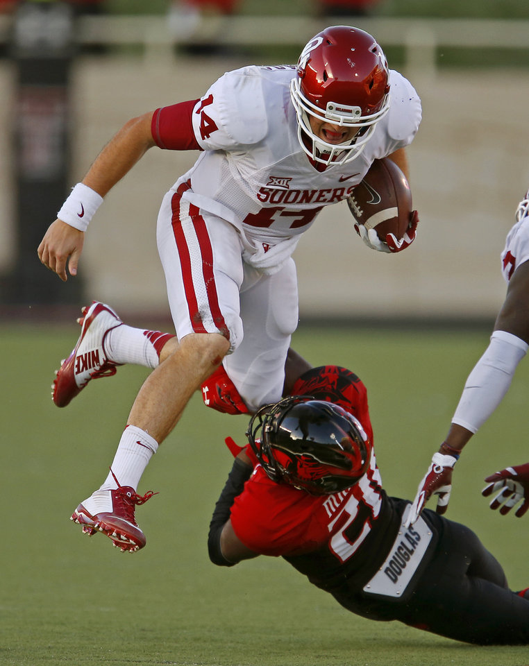 Photo - Oklahoma's Cody Thomas (14) leaps past Texas Tech's Michael Coley (21) during the college football game between the University of Oklahoma Sooners (OU) and the Texas Tech Red Raiders at Jones AT&T Stadium in Lubbock, Texas, Saturday, November 15, 2014.  Photo by Bryan Terry, The Oklahoman