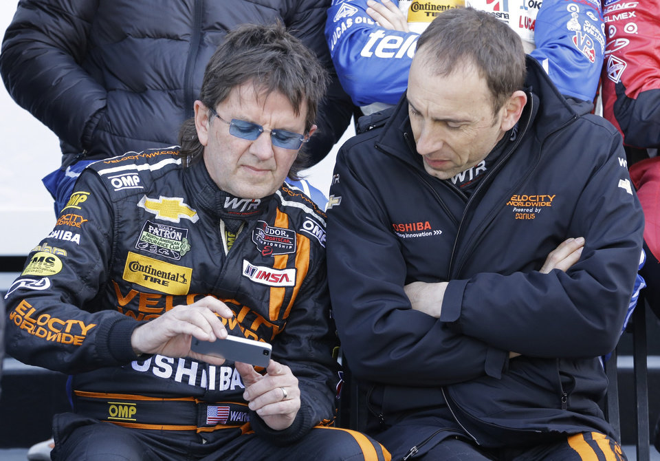 Photo - Drivers Wayne Taylor, left, and Max Angelelli, of Italy, look over a smart phone after practice for the IMSA Series Rolex 24 hour auto race at Daytona International Speedway in Daytona Beach, Fla., Friday, Jan. 24, 2014.(AP Photo/John Raoux)
