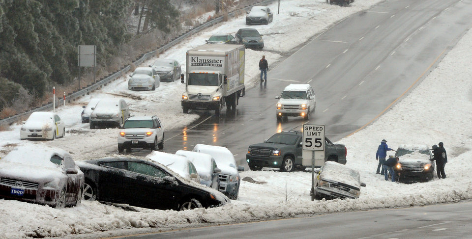 Photo - Wrecked and abandoned vehicles litter Hwy 70 near the Angus Barn in Raleigh, N.C., Thursday Feb. 13, 2014. While the core of the storm that brought snow, sleet and freezing rain to the state headed north into Virginia on Thursday, the tail end of the system was expected to dump even more snow on the state. (AP Photo/The News & Observer, Chuck Liddy)