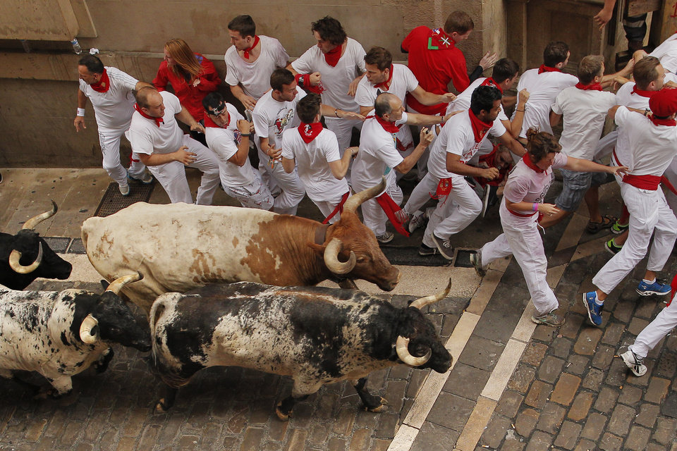 Photo - Torrestrella fighting bulls and revelers run during the running of the bulls of the San Fermin festival, in Pamplona, Spain, Monday, July 7, 2014. Revelers from around the world arrive to Pamplona every year to take part on some of the eight days of the running of the bulls glorified by Ernest Hemingway's 1926 novel