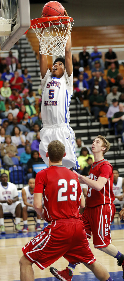 Photo - Millwood senior forward Ashford Golden stuffs the basketball into the hoop, driving past  coverage by Howe defenders Stephen Helmandollar, #23, and Nick Smallwood, #3 during the second half of the Class 2A boys basketball quarterfinal game between Millwood and Howe at Oklahoma City University  on Thursday night, Mar. 13, 2014. Photo by Jim Beckel, The Oklahoman