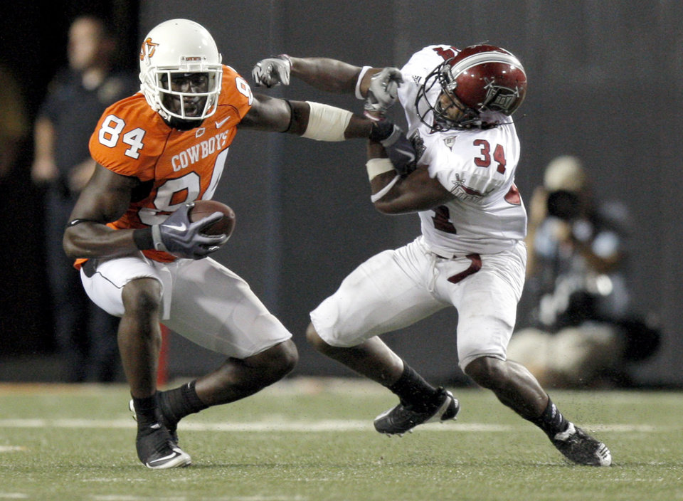 Photo - OSU's Hubert Anyiam stiff arms Troy's KeJuan Phillips during the college football game between the Oklahoma State University Cowboys (OSU) and the Troy University Trojans at Boone Pickens Stadium in Stillwater, Okla., Saturday, Sept. 11, 2010. Photo by Sarah Phipps, The Oklahoman