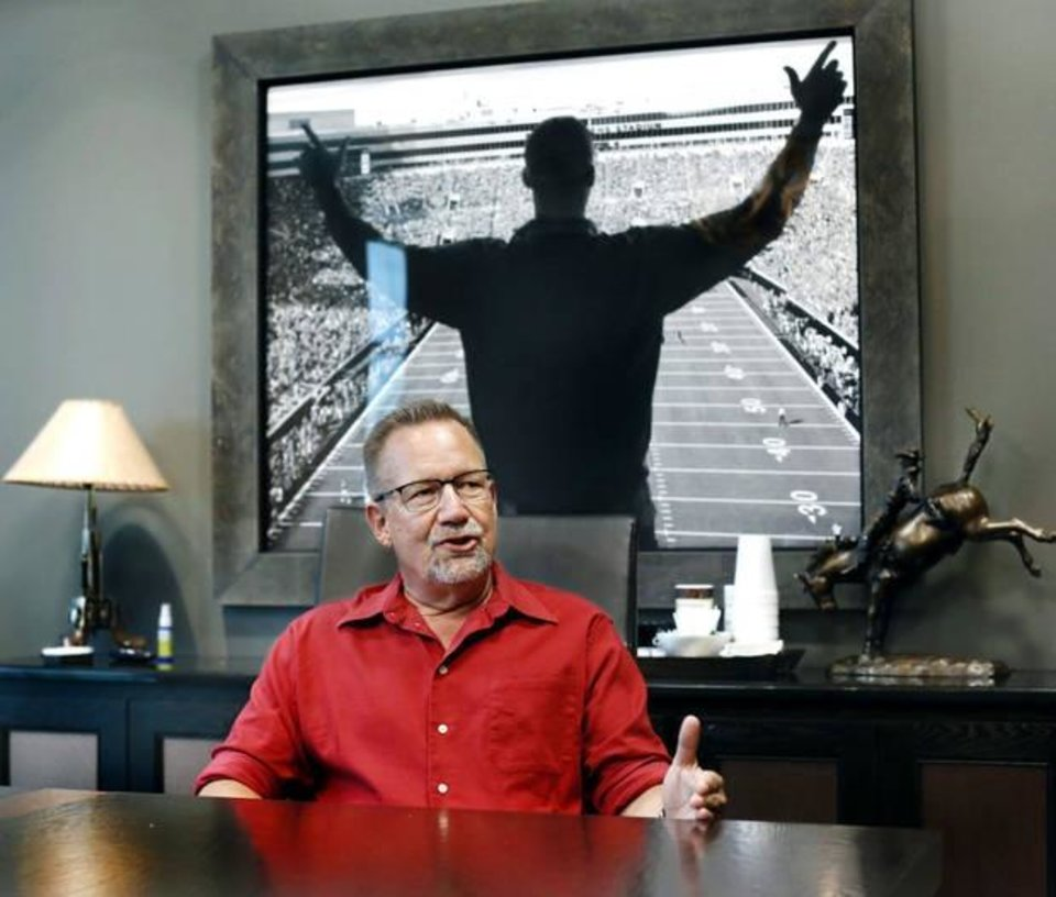 Photo -  Mark Dougherty, appraisal underwriter for Gateway First is shown at company headquarters in Jenks. Behind him is a large framed photo of Gov. Kevin Stitt celebrating a Cowboys touchdown at an Oklahoma State University football game in Boone Pickens Stadium. [Jim Beckel for The Oklahoman]