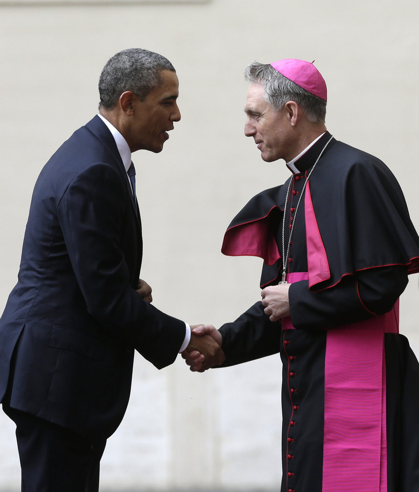 Photo - President Barack Obama, left, is welcomed by Archbishop George Gaenswein, prefect of the papal household, as he arrives at the Vatican to meet Pope Francis, Thursday, March 27, 2014. Obama is the ninth president to make an official visit to the Vatican. His audience marks a change of pace for the president, who has devoted the past three days of a weeklong, four-country trip to securing European unity against Russia's aggressive posture toward Ukraine. (AP Photo/Alessandra Tarantino)