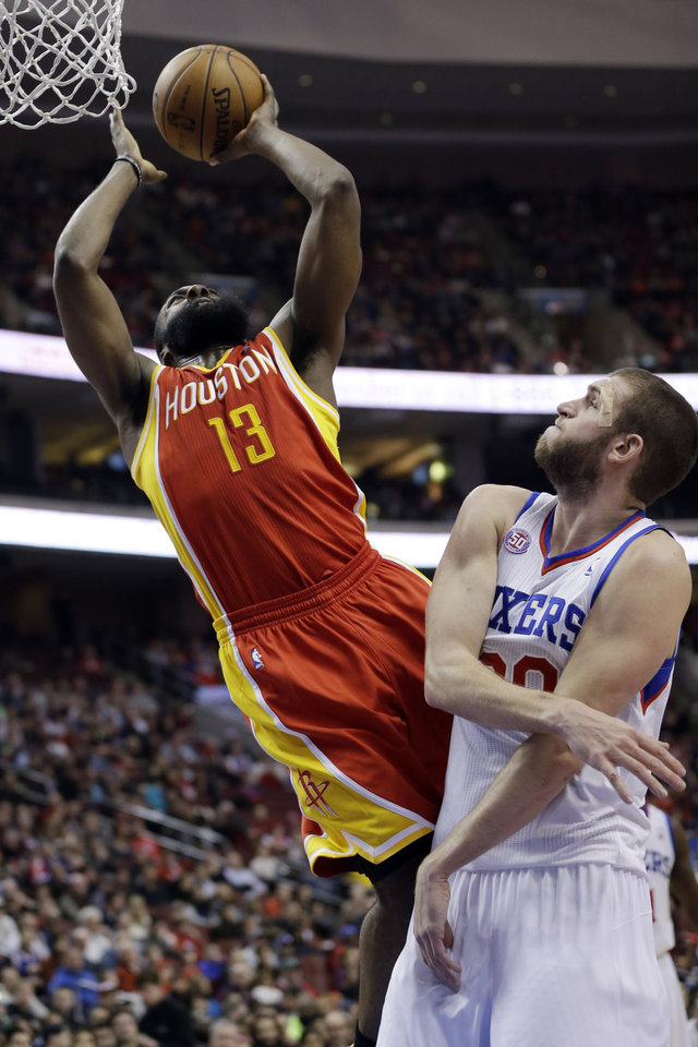 Photo - Houston Rockets' James Harden, left, goes up for a shot against Philadelphia 76ers' Spencer Hawes in the first half of an NBA basketball game, Saturday, Jan. 12, 2013, in Philadelphia. (AP Photo/Matt Slocum)