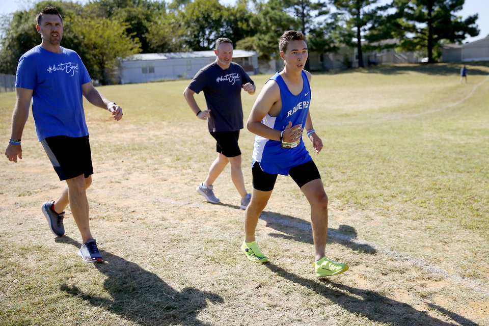 Photo - Newcastle runner Caleb Freeman, who was injured in a 2017 car crash, is followed by his father Jeremy Freeman, right, and Shawn Wright as he runs a cross country race at Carl Albert in Midwest City, Okla., Tuesday, Oct. 8, 2019. This was Caleb Freeman's first cross country race since getting injured in a 2017 car wreck. [Bryan Terry/The Oklahoman]