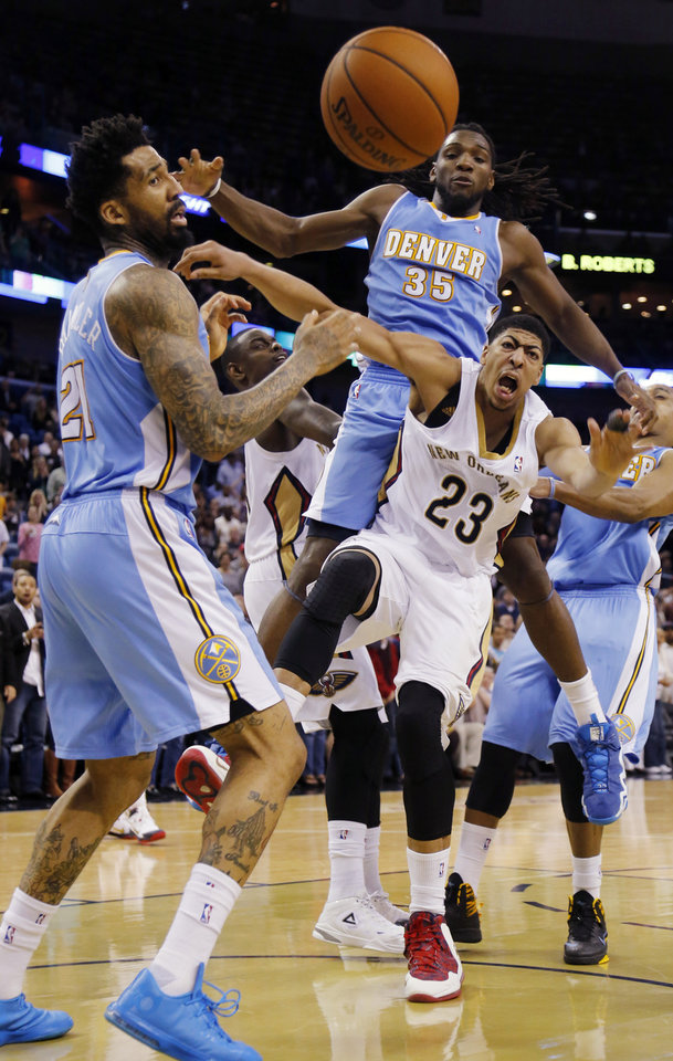 Photo - New Orleans Pelicans power forward Anthony Davis (23) fights for a loose ball with Denver Nuggets small forward Wilson Chandler (21), and Denver Nuggets power forward Kenneth Faried (35) in the second half of an NBA basketball game in New Orleans, Sunday, March 9, 2014. The Pelicans defeated the Nuggets 111-107. Davis scored 32-points in the Pelicans victory. (AP Photo/Bill Haber)