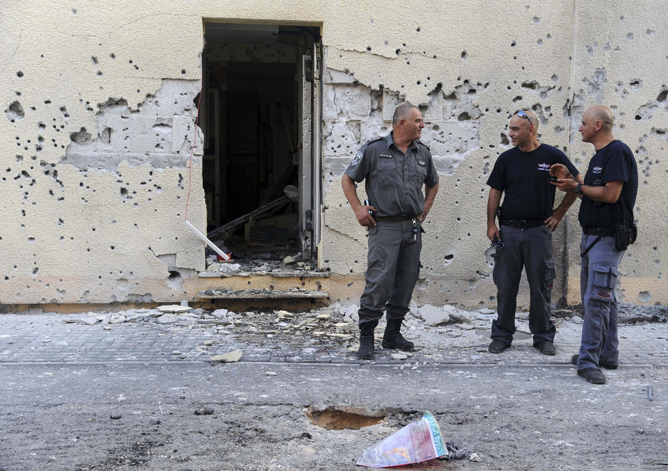 Photo - Israeli policemen stand in front of a house damaged by a rocket fired from Lebanon in Shavei Tzion outside Nahariya in northern Israel, Thursday, Aug. 22, 2013. Military spokesman Lt. Col. Peter Lerner said Thursday that three rockets landed in northern Israel, while one was shot down. (AP Photo/Jinipix) ISRAEL OUT