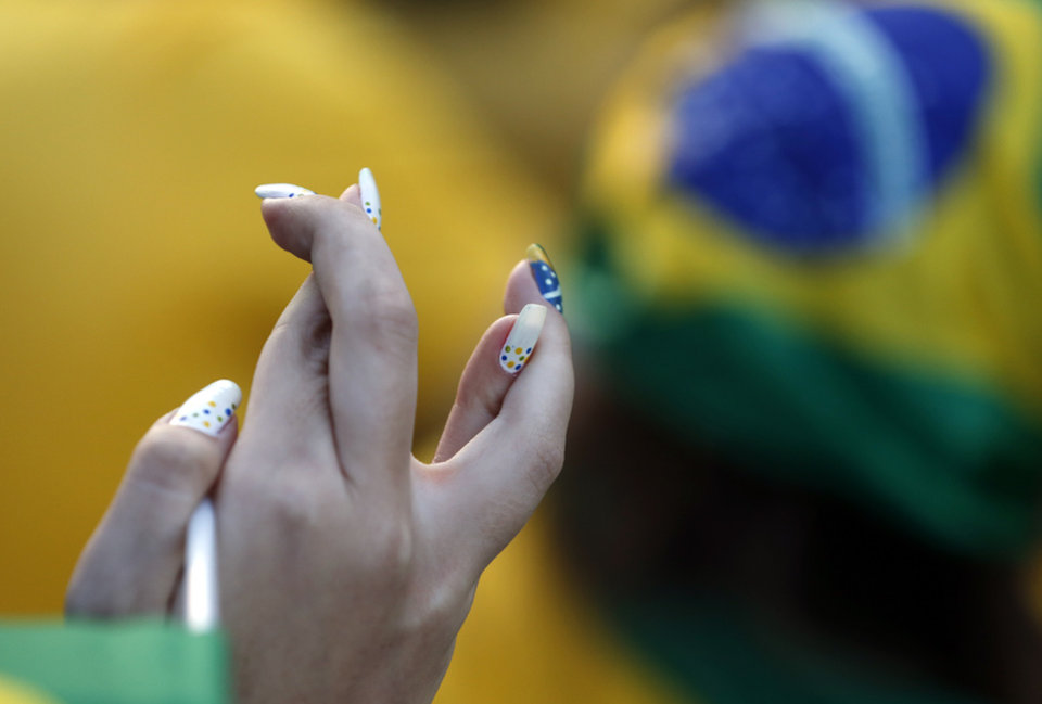 Photo - A Brazil fan crosses her fingers as Brazil takes a free kick in the first half of the World Cup opening match against Croatia in group A at Itaquerao Stadium in Sao Paulo, Brazil, Thursday, June 12, 2014. Thursday is a holiday in Sao Paulo and everybody is celebrating the start of the international soccer tournament. Fans dressed in yellow and green greeted each other, often yelling,