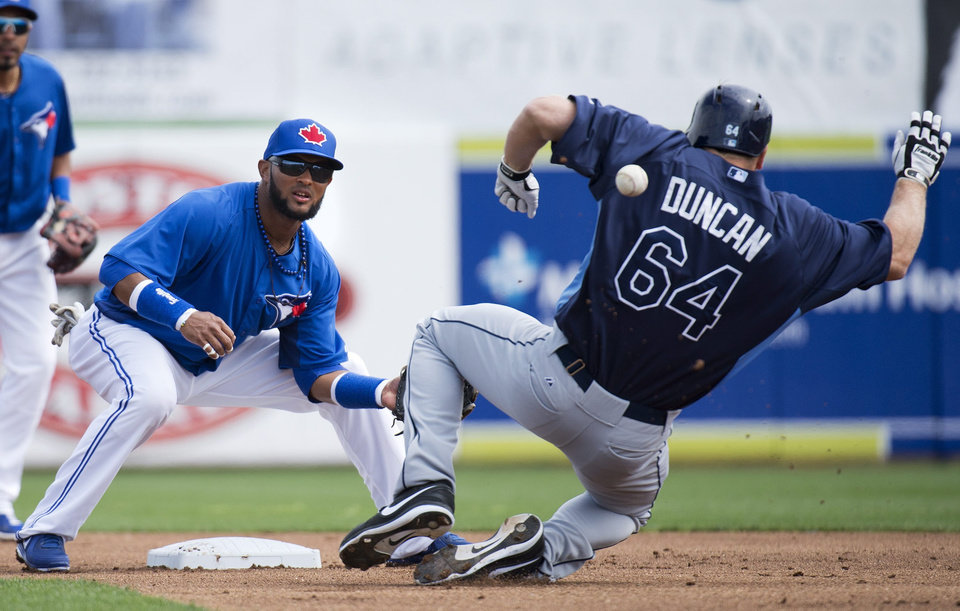 Toronto Blue Jays second baseman Emilio Bonifacio, left, waits for the throw as Tampa Bay Rays' Shelley Duncan slides during the first inning of a spring training baseball game Friday, March 1, 2013, in Dunedin, Fla. (AP Photo/The Canadian Press, Nathan Denette)