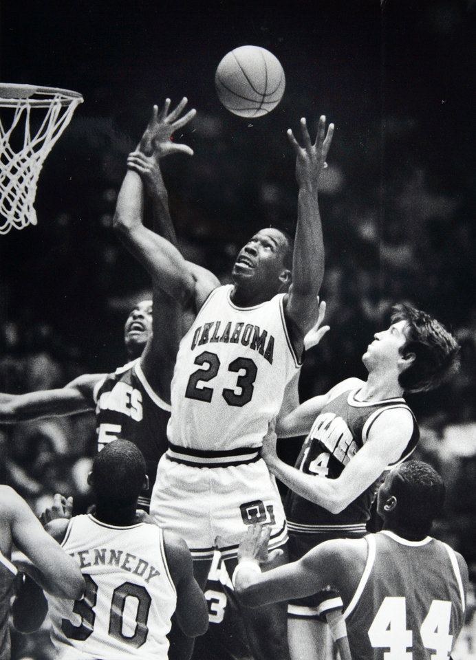 Photo - Former OU basketball player Wayman Tisdale. Barry Stevens has his arm, but Wayman Tisdale has the rebound. Wayman Tisdale is closing in on Alvin Adams All-Time rebound mark here out-rebounding Barry Stevens(l) and Jeff Hornacek (R). Staff photo by Doug Hoke. Photo taken 2/13/1985, Photo published 2/14/1985 in The Daily Oklahoman. ORG XMIT: KOD