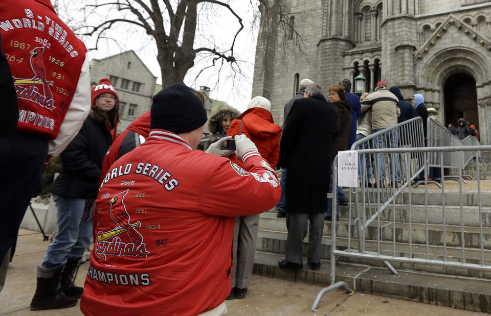Photo - Dave Ebert takes a photo of the line of people as he waits along with them outside Cathedral Basilica of Saint Louis to pay their respects during the public visitation for former St. Louis Cardinals baseball player Stan Musial, Thursday, Jan. 24, 2013, in St. Louis. Musial, one of baseball's greatest hitters and a Hall of Famer with the Cardinals for more than two decades, died Saturday, Jan. 19, 2013. He was 92. (AP Photo/Jeff Roberson)
