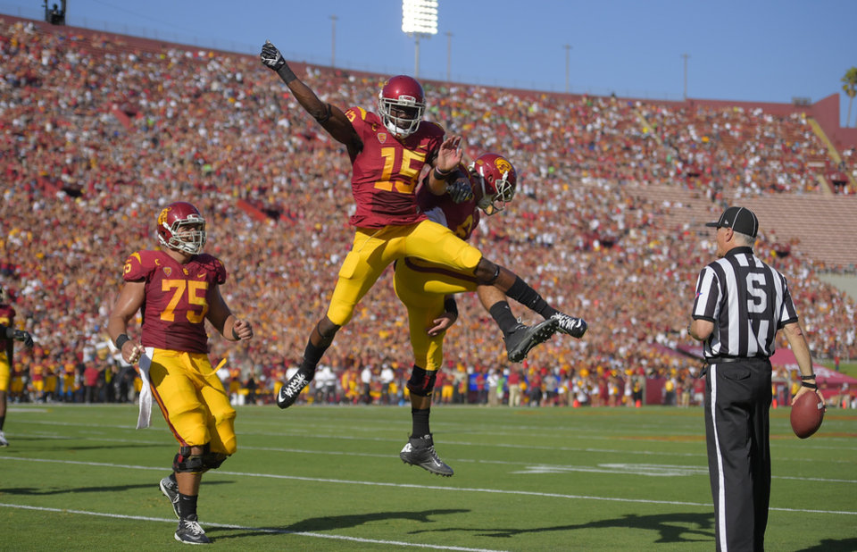 Photo - Southern California wide receiver Nelson Agholor, second from left, celebrates with quarterback Cody Kessler as center Max Tuerk, left, looks on after scoring a touchdown during they first half of an NCAA college football game against Fresno State, Saturday, Aug. 30, 2014, in Los Angeles. (AP Photo/Mark J. Terrill)