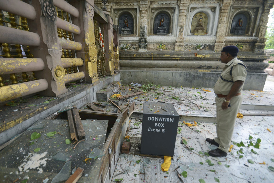A security officer inspects the site of an explosion on the campus of the Mahabodhi Temple, the Buddhist Great Awakening temple, in Bodhgaya, about 130 kilometers (80 miles) south of Patna, the capital of the eastern Indian state of Bihar, Sunday, July 7, 2013. A series of small blasts hit three Buddhist temples in eastern India early Sunday, injuring at least two people, police said. (AP Photo/Manish Bhandari)